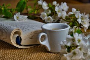 cup of coffee next to book with flowers around