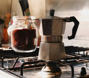 Moka pot on stove with jar of coffee grounds behind it