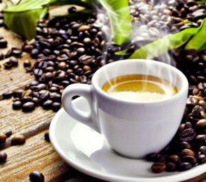 cup of coffee on plate with coffee beans around and steam