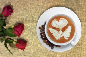 cup of espresso with roses and coffee beans
