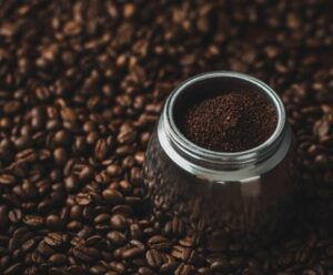 canister of ground coffee sitting on a bed of coffee beans