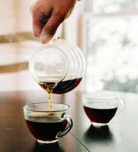 two cups of coffee, carafe of coffee being poured into one cup