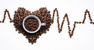 Coffee cup full of coffee beans with coffee bean heart beat