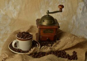 cup of coffee beans next to old fashion coffee grinder