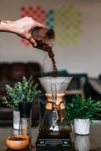 coffee grounds being poured into a chemex coffee maker on a scale