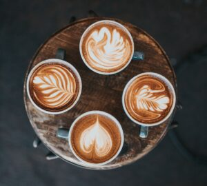 four cups of decorative coffee on a tree stump, top view