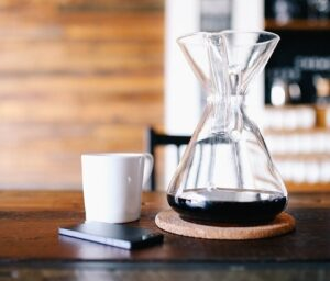Coffee cup next to carafe of coffee