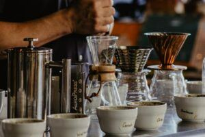 French Press, chemex, and pour over coffee makers with coffee cups lined in front