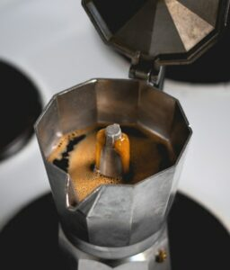 Moka Pot with to open showing coffee brewing inside, on stovetop