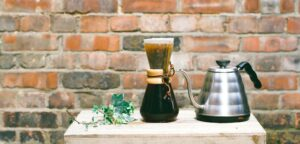 Chemex coffee maker next to coffee carafe on table with plant