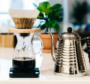 Pour over coffee maker next to coffee carafe on counter