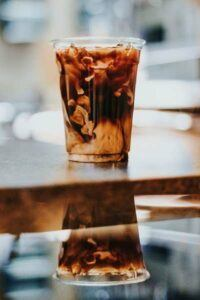 iced coffee in a clear glass sitting on a mirrored table with reflection below