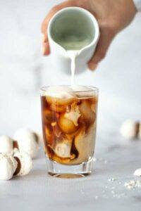 milk or cream being poured into a cup of iced coffee, coffee and milk mixing in a glass sitting on a table