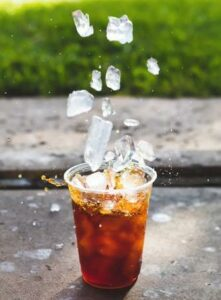 Iced coffee, ice falling into coffee cup, cup sitting on the ground with grass in background