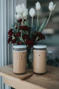 two covered jars of iced coffee, sitting on a table with tulips in the background