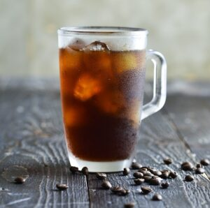 iced coffee in a mug on a table with coffee beans