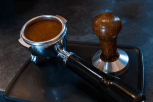 portafilter filled with espresso coffee grounds, tamper