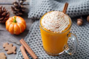 Pumpkin latte topped with whipped cream, cinnamon sticks, pumpkin on a kitchen towel background