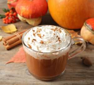 pumpkin spice latte in a clear mug, pumpkins in background on wooden table