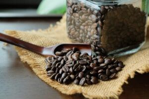 roasted coffee bean in spoon on burlap cloth, glass canister full of roasted coffee beans