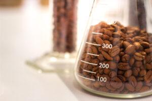 coffee beans in beaker, coffee beans in flask with white light background
